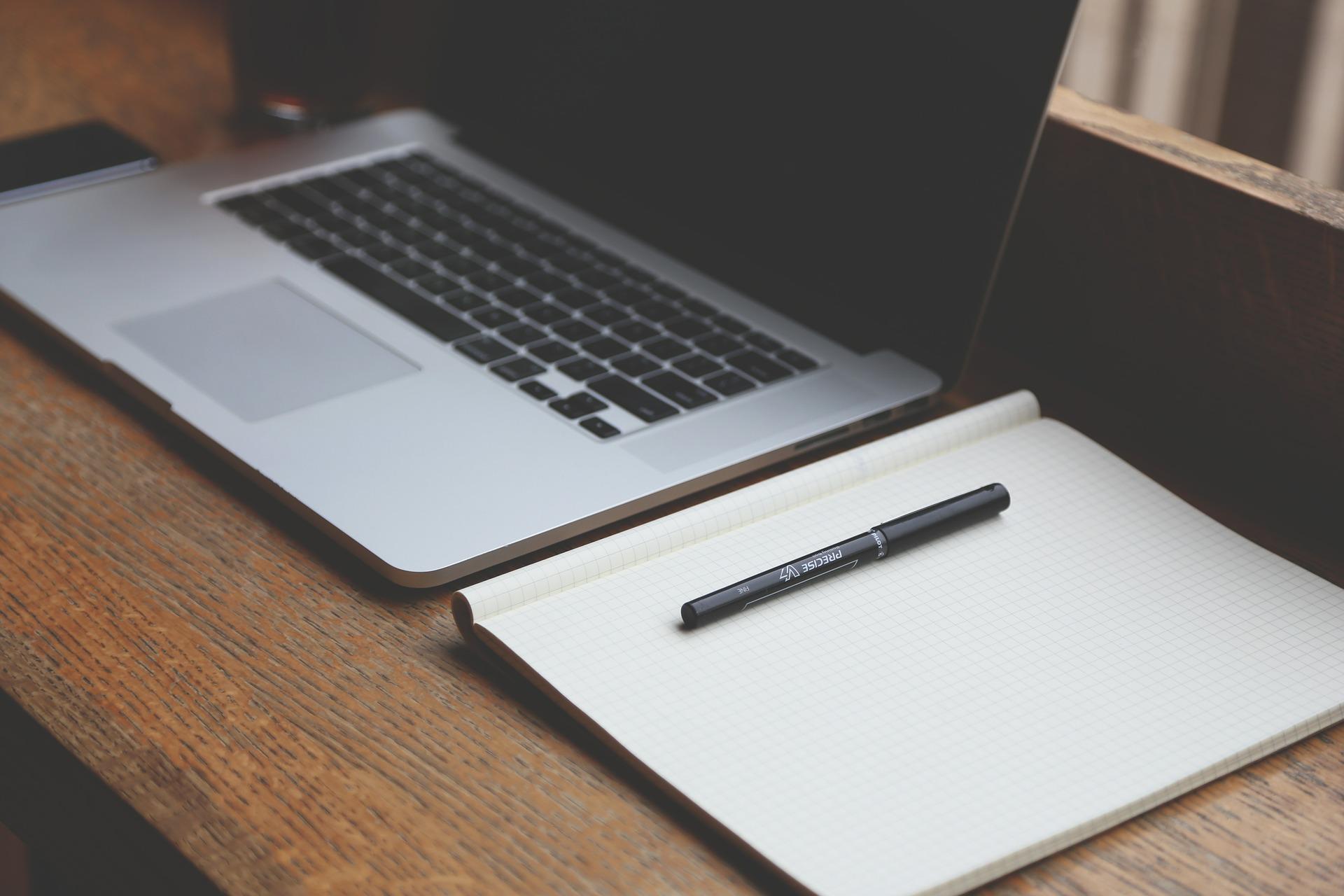 Auftragsformular: Notebook und Block auf Holztisch